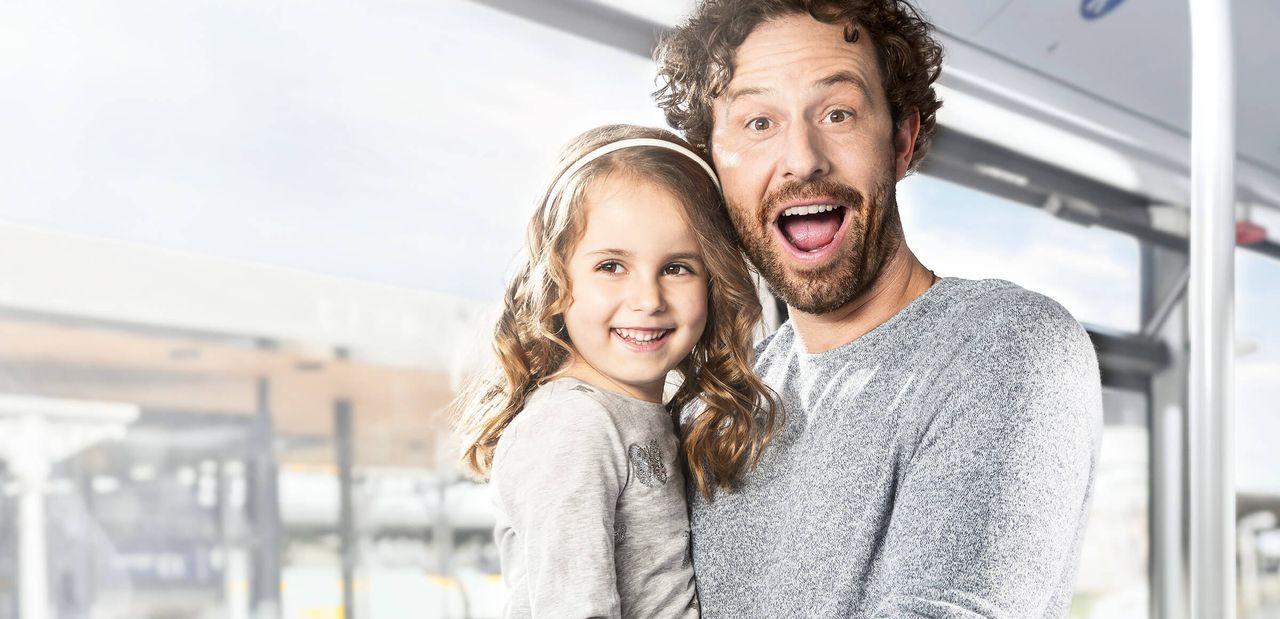 Mann mit Kind auf dem Arm in der Bahn