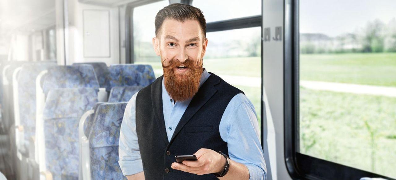 Mann mit Vollbart und Handy in der Hand