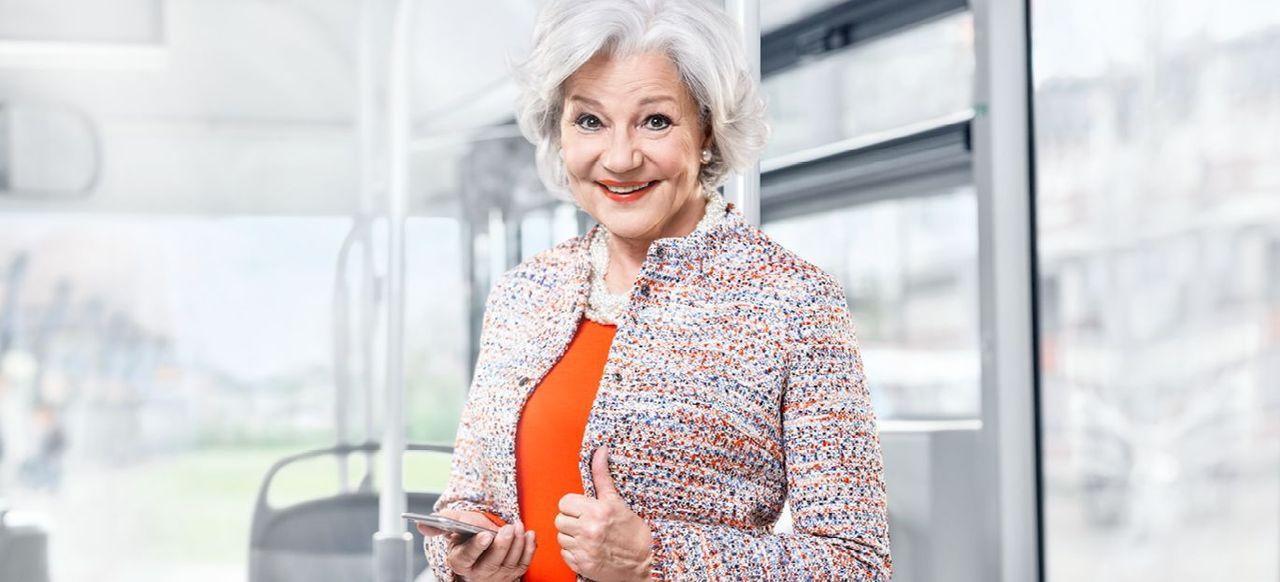 Ältere Dame lächelt und hat ein Handy in der Hand